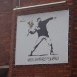 Another brick wall in Bristol with Banksy art.